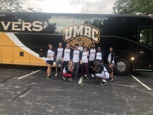 Student & staff in front of UMBC Bus